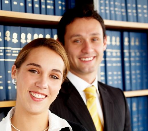 Egy nő és férfi ránk mosolyog, a háttérben jogi könyvekkel teli polc.