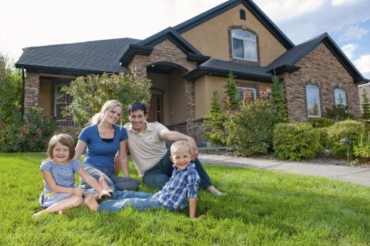 Egy négytagú család egy nagy családi ház előtt a fűben ül.