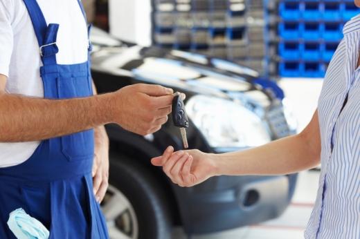 Egy szerelő átadja a kulcsot az tulajdonosnak, mögöttük az autó.