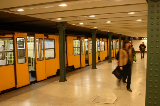 A metróállomáson leszállnak az emberek a sárga metróról.