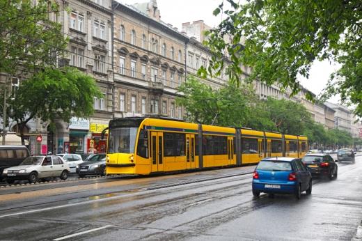 Egy sárga villamos esőben a városban, több sávos úton.