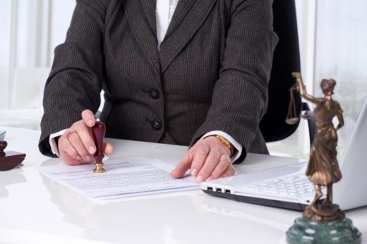 Egy öltönyös nő pecsétel egy szerződést.