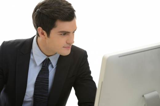 Egy öltönyös férfi nézi a monitorját.
