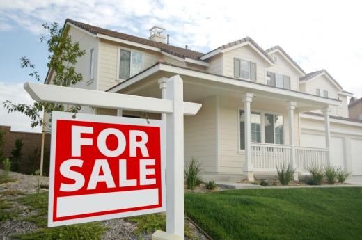 Egy amerikai típusú fehér családi ház, FOR SALE feliratú táblával.