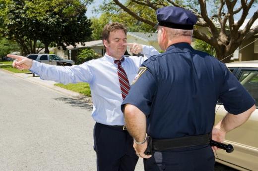A rendőr előtt áll a sofőr és az ujját az orrához érinti.