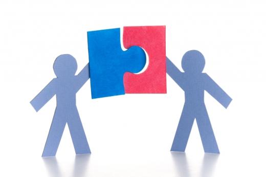 Két papír ember összeilleszt egy piros és egy kék puzzle darabot.