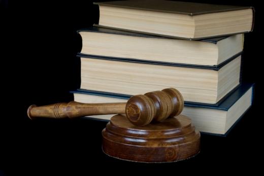 Egy bírói kalapács négy törvénykönyv előtt.