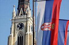 Egy toronyóra előtt szerb zászló.