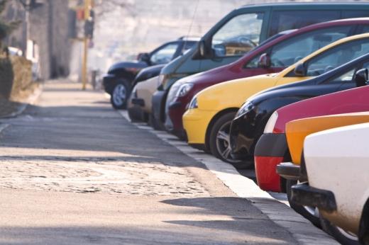 Kép egy hosszú járdáról ami mellett autók sorban parkolnak.