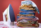 Egy vasaló és mellette összehajtva egymáson a vasalt ruhák.