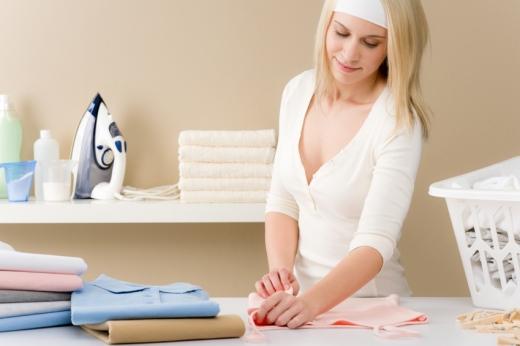 Egy nő vasalás után hajtogatja a ruhákat.