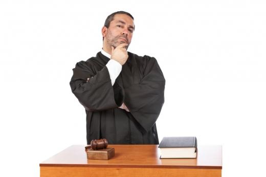 Egy bíró állát fogva áll, egy asztal előtt, amin egy törvénykönyv és egy bírói kalapács van.