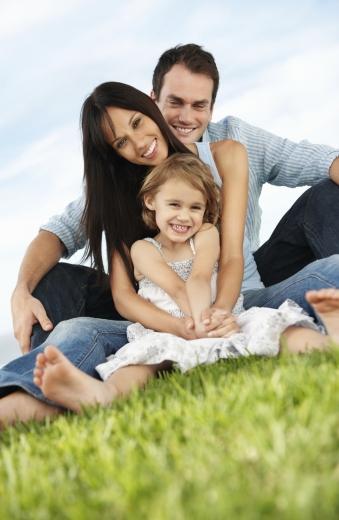 Egy három tagú család egymás előtt ül a fűben.