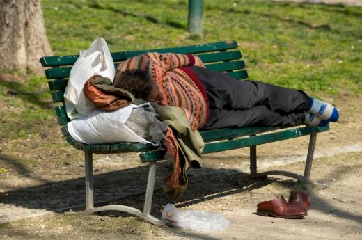 Egy hajléktalan alszik egy zöld padon, a cipője a pad előtt van.
