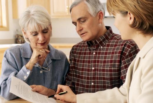 Egy nő egy nyomtatványt mutat egy idősebb házaspárnak.