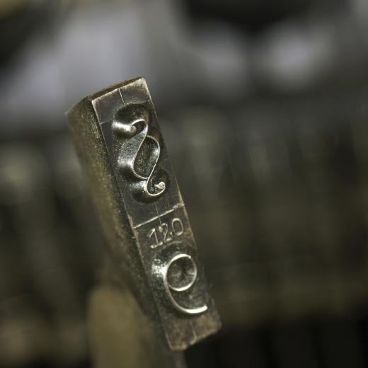 Egy írógép billentyűje, amin egy paragrafus és egy kilences jel van.