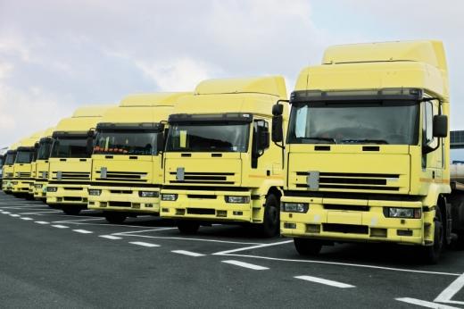Több sárga kamion sorban parkol egymás mellett.