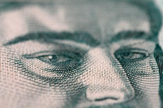 Egy papírpénzen lévő férfi szemére közelít a kép.