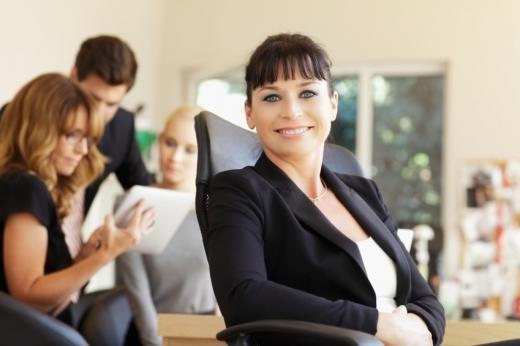 Egy nő elégedetten ül a székében, mögötte kollégái beszélgetnek.