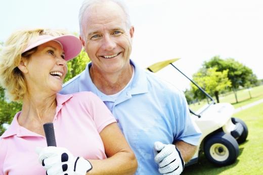 Egy pár golfruhában egy golfautó előtt mosolyog.