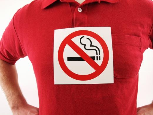Egy piros pólós férfin egy ne dohányozz tábla.