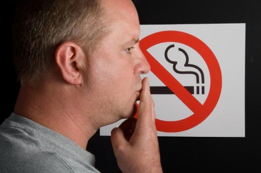Egy férfi egy ne dohányozz tábla előtt.