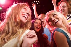 Fiatal lányok mosolyogva táncolnak egy buliban.