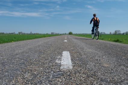Egy úton fiú megy biciklivel.
