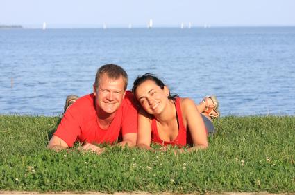 Egy fiatal pár egy tó előtt a fűben hason fekszenek és ránk mosolyognak.