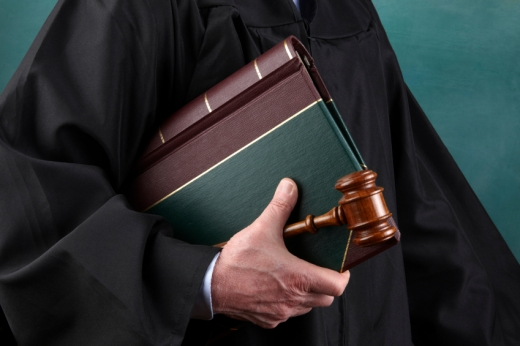 Egy bíró a hóna alatt bírói kalapáccsal és törvénykönyvvel.
