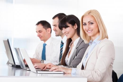 Két férfi és két nő, egymás mellett a laptopja előtt dolgozik. Oldalról látjuk őket.