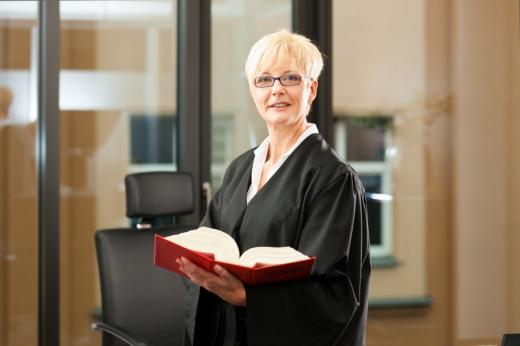 Egy bírónő kezében egy törvénykönyv.
