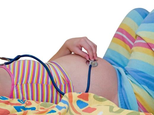 Egy terhes nő sztetoszkópot tart a hasára.