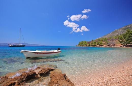 Egy tengerparton egy csónak és egy vitorlás.