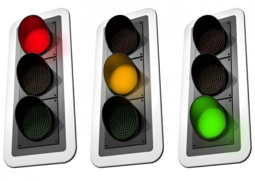 Három jelzőlámpa egymás mellett: piros, sárga és zöld.
