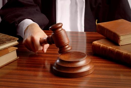 Egy bíró keze, amint lecsap a bírói kalapácsával.