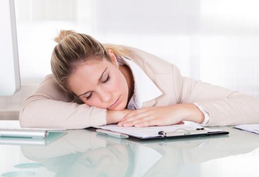 Egy nő az íróasztalára dőlve alszik.