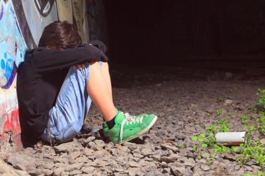 Egy fiú a kavicsos földön ül, háttal egy graffitis falnak támaszkodva. szomorúan.
