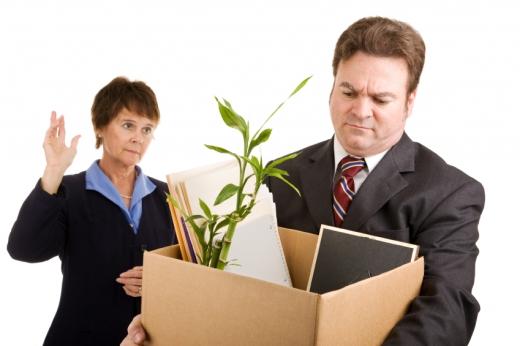 Egy férfi papírdobozba elviszi a munkahelyi dolgait, egy nő a háttérben int neki.