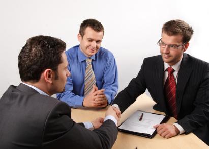 Két öltönyös férfi egy asztalnál kezet fognak, egy harmadik nyakkendős nézi őket.