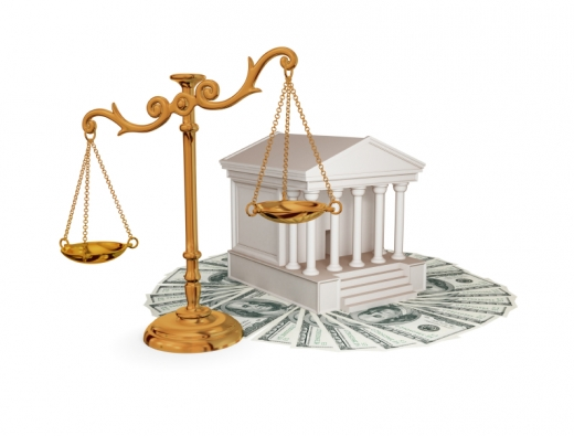 Egy aranyszínű jogi mérleg mögött egy bíróság, ami papírpénzeken van.