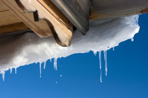 Egy tető aljáról lóg le a hó és a jégcsapok.