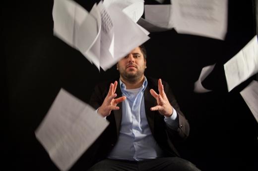 Egy öltönyös férfi ülve felénk dob egy csomó papírlapot.