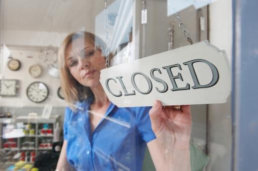 Egy nő az órás boltban elfordítja a táblát CLOSE feliratra.