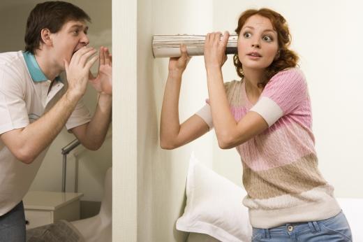 Egy férfi kiabál a fal egyik feléről, a lány pedig összetekert újságot tartva a falhoz, hallgatózik.