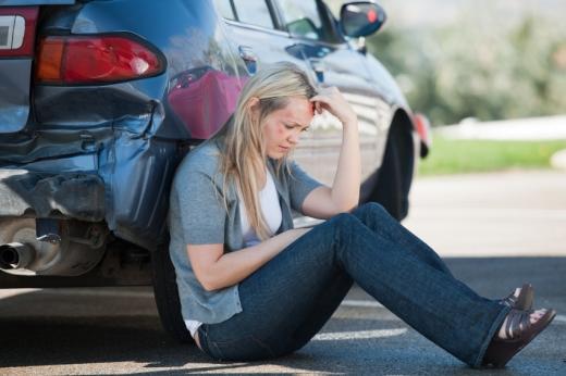 Egy nő az úton ül, háttal nekidőlve a összetört autójának.