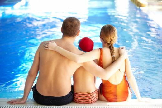 Egy háromtagú család fürdőruhában a medence szélén ül, háttal nekünk.