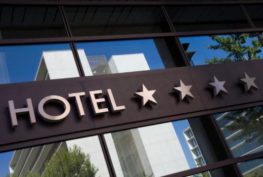 Egy üveges bejáratú épület négycsillagos hotel felirattal.