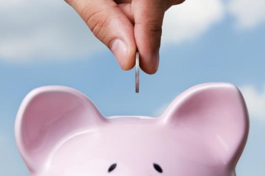 Egy kéz egy aprópénzt dob egy malacperselybe.