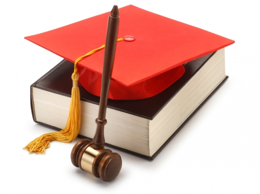 Egy törvénykönyv, rajta egy ballagási sapka és mellette egy bírói kalapács.